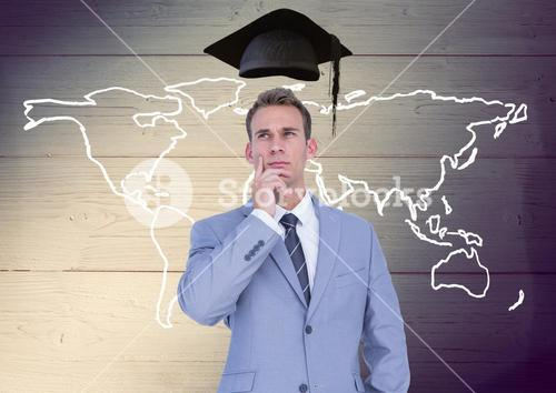 Businessman with mortarboard above head and world map against wooden background