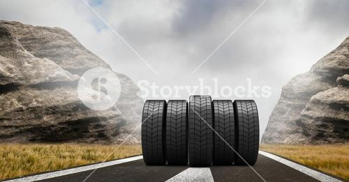 Tyres on road against cloudy sky and rocks