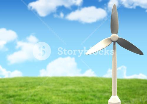 Windmill against green grass and sky in the background