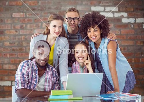 Confident students with laptop and book smiling at camera