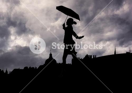 Woman holding umbrella walking against stormy clouds