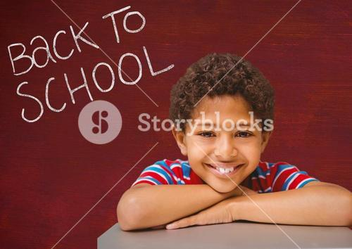 Portrait of happy boy leaning on table with back to school text