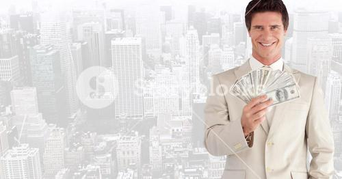 Portrait of smiling businessman holding fanned currency