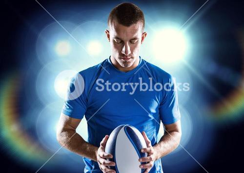 Rugby player holding ball against illuminated background