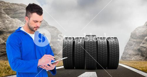 Mechanic writing on clipboard with tyres on road in background