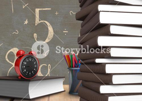 Alarm clock on a book with number and mathematical symbols on chalkboard in background