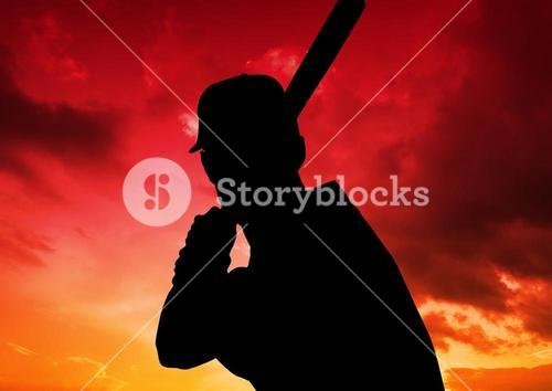 Silhouette of baseball player against colorful sky