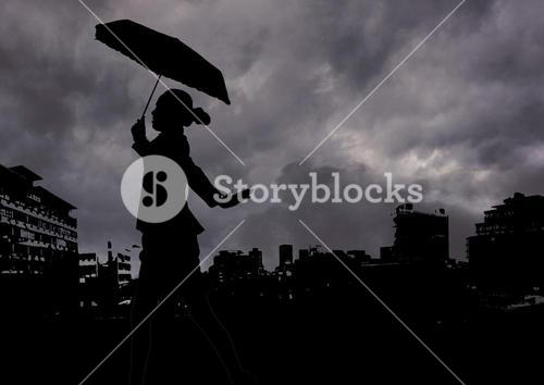Woman holding umbrella walking against stormy clouds and cityscape