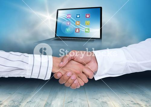 Businesspeople shaking hands with various icon over laptop screen in background
