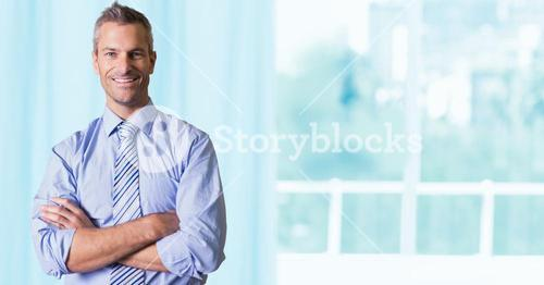 Businessman standing against glass window