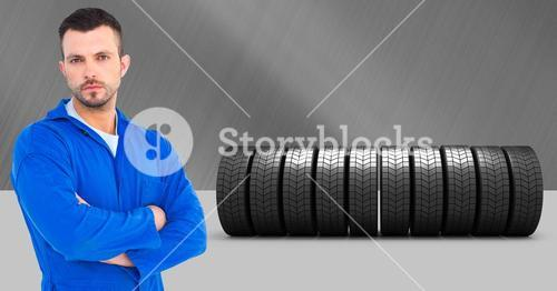 Mechanic standing with arms crossed with tires in background