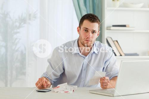 Businessman checking bills in his homeoffice