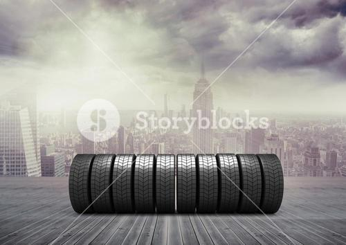 Stack of tyres on wooden walkway against cityscape background