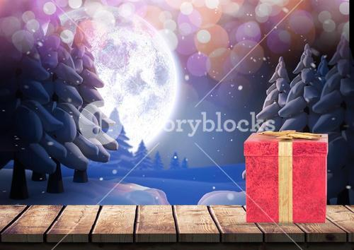 Gift box on wooden plank against snowy background