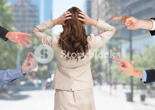 Hands blaming a stressed woman against city buildings in background