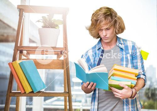 Boy reading books against school in background