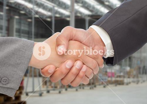 Businessman shaking hands against warehouse in background
