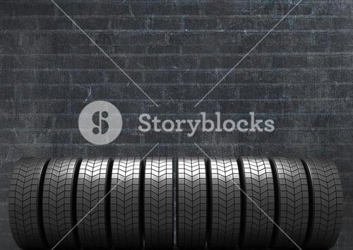 Stack of tyres against black brick background