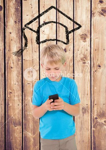 Boy using mobile phone with graduation hat on wooden background