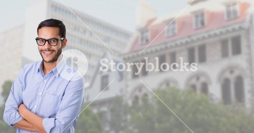 Man standing with his hands crossed against building in background