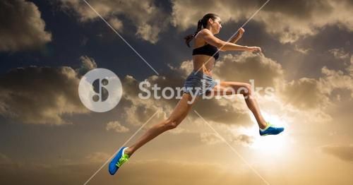 Athlete practicing high jump against sky in background