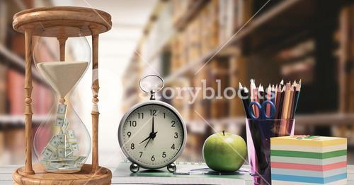 Hour glass, alarm clock, apple and pen holder against library in background