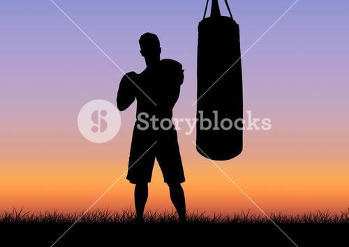 Silhouette of boxer and punching bag against sunset in background