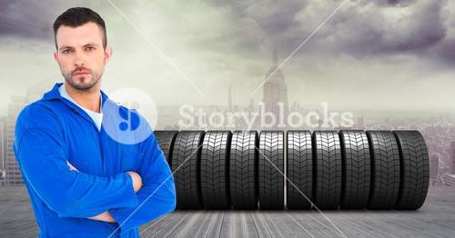 Mechanic standing with his aims crossed with stack of tyres in background