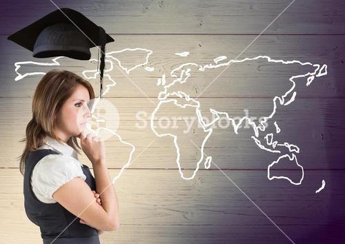 Thoughtful businesswoman with graduation cap against world map in wooden background