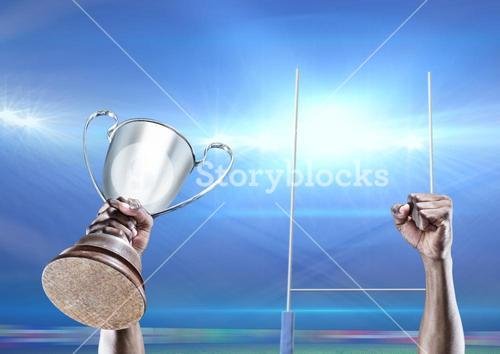 Player lifting trophy against goal post in background