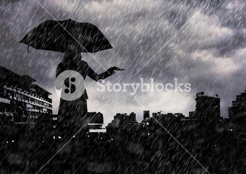 Silhouette of woman holding an umbrella against cityscape