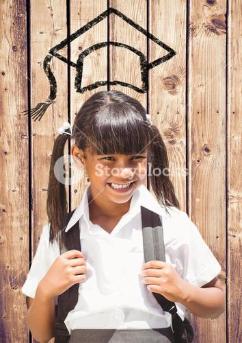 School girl with graduation cap on wooden plank background