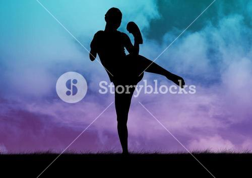 Silhouette of woman practicing kick boxing against  sky in background