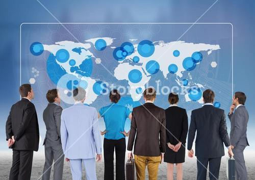 Team of business executives looking at world map