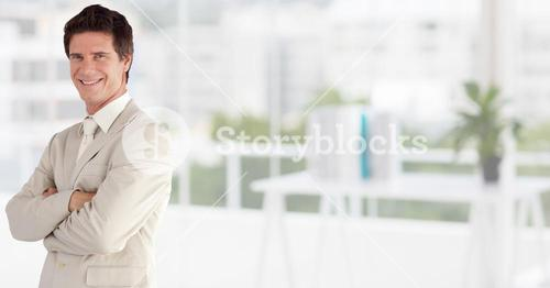 Portrait of a happy Businessman standing with arms crossed in office