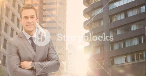 Portrait of a confident businessman standing with arms crossed with buildings in background