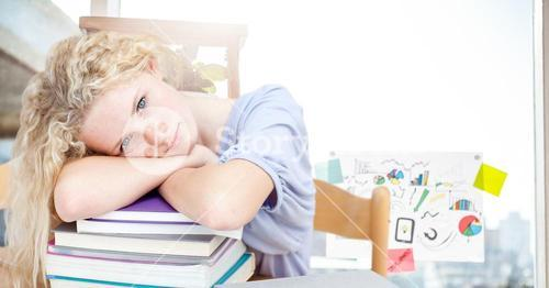Portrait of a girl resting her head on stack of books in classroom