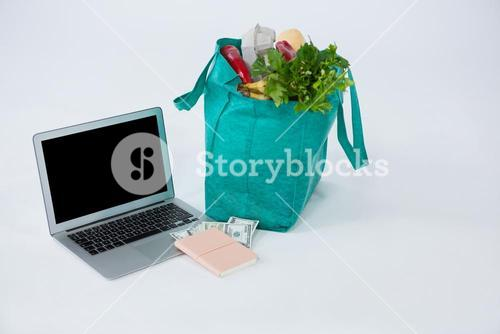 Grocery bag with banknotes and laptop