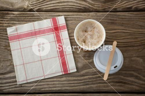 Coffee in disposable cup with tissue paper