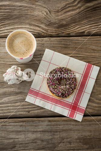 Doughnut and coffee on wooden plank