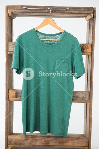 Green t-shirt hanging on wooden frame