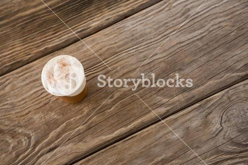 Coffee in disposable cup on wooden table