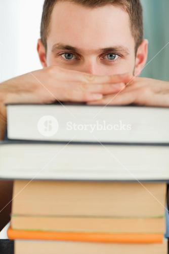 Close up of student hiding behind a pile of books