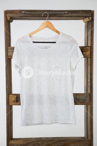 White t-shirt hanging on wooden frame