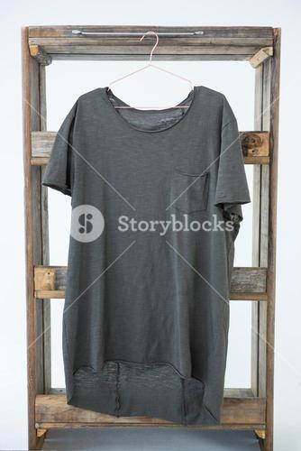 Grey t-shirt with pocket hanging on wooden frame
