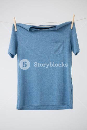 Blue t-shirt with pocket hanging on clothes line