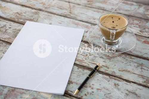 Cup of coffee with pen and paper