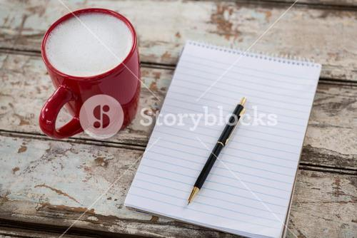 Cup of coffee with blank notepad and pen