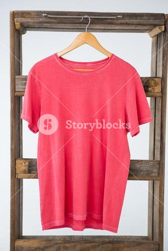 Pink t-shirt hanging on wooden frame