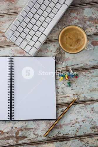Coffee, pushpin, pencil, computer keyboard and organiser on wooden table
